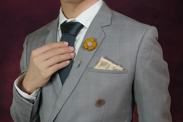 Traje a cuadros gris, corbata, broche, pañuelo