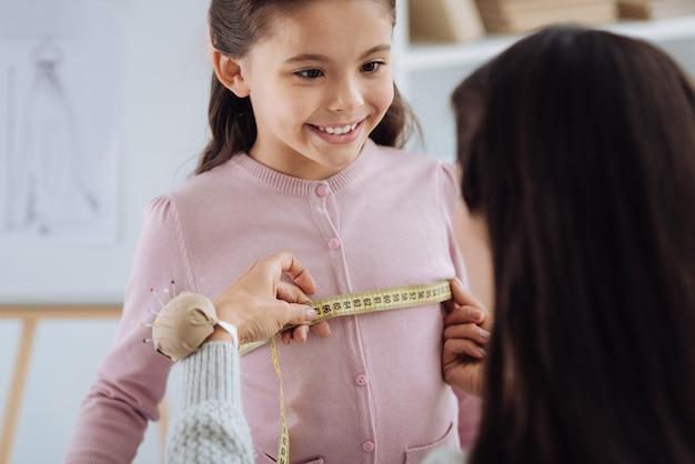 Traje especial. agradable sastre profesional usando un anuncio de cinta métrica haciendo medidas para ella mientras prepara una sorpresa