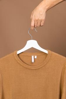 Traje con etiqueta de ropa en percha blanca
