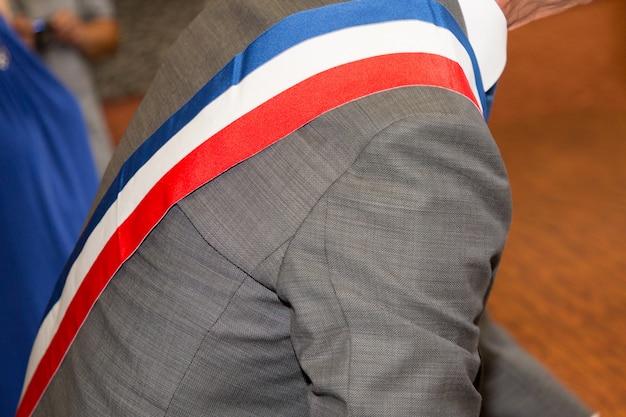 Traje gris alcalde francés durante la celebración oficial con signo de bufanda