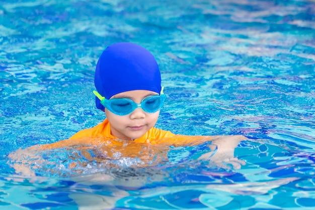 Traje húmedo, un niño asiático con gafas de natación es nadar en una piscina.
