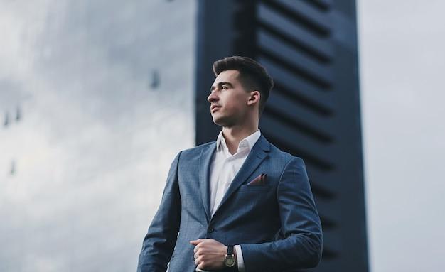 Traje de joven exitoso sobre edificio de oficinas. hombre elegante posando en la ciudad
