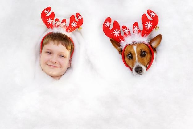 Traje de lindos amigos en un reno y un sombrero de santa acostado en la nieve