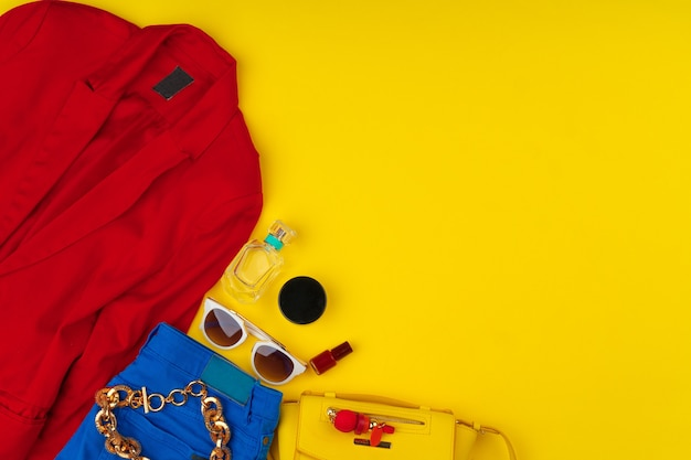 Traje de mujer de moda con accesorios sobre fondo amarillo brillante