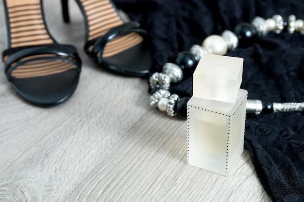 Traje de mujer. vestido de encaje negro, sandalias, collar y perfume.