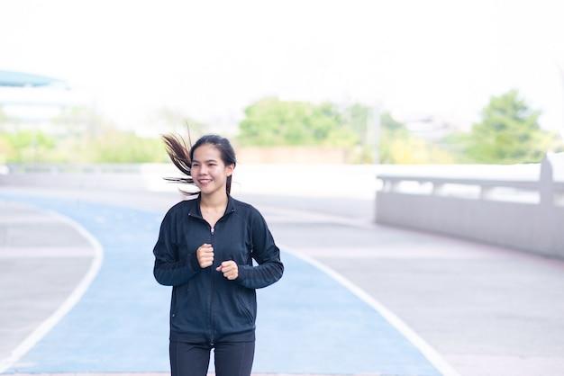 Traje negro de la mujer joven hermosa asiática con feliz correr o trotar en la pista de atletismo.