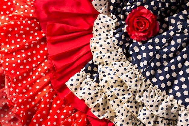 Trajes de flamenca en rojo azul con lunares y rosa roja.