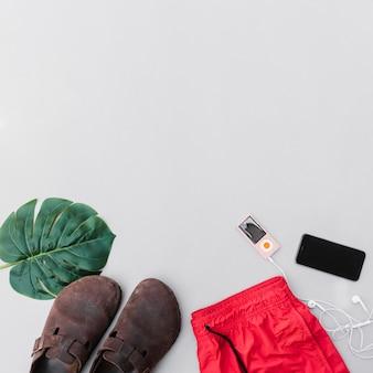Trajes, par de zapatos, hoja, teléfono móvil y reproductor de mp3 sobre fondo gris