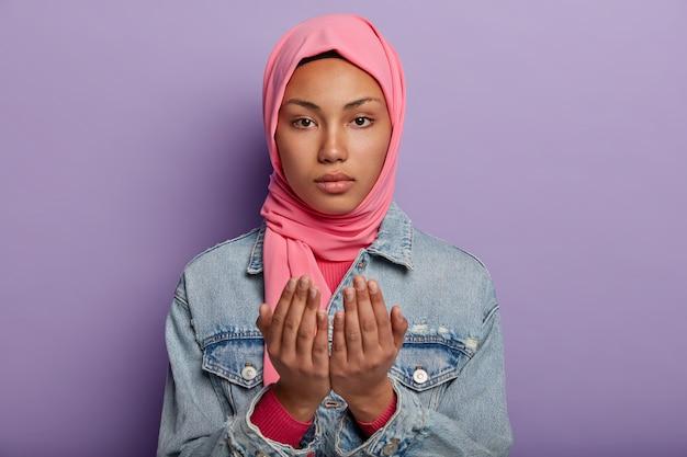 Tranquila y atractiva mujer árabe mantiene las palmas de las manos en gesto de oración, viste hijab rosa y chaqueta vaquera