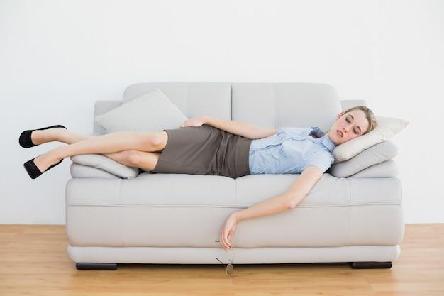 Tranquila empresaria elegante durmiendo mientras está acostado en su sofá