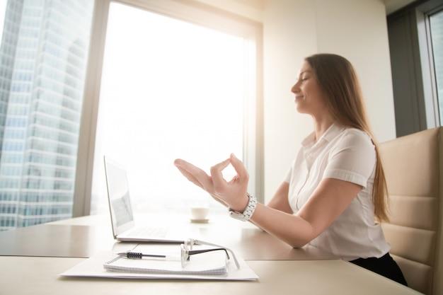 Tranquila empresaria pacífica practicando yoga en el trabajo, meditando en la oficina