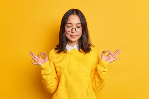 Tranquila joven asiática muestra zen o bien signo medita de buen humor se encuentra con los ojos cerrados, usa suéter casual y gafas.