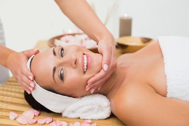 Tranquila morena disfrutando de un masaje facial