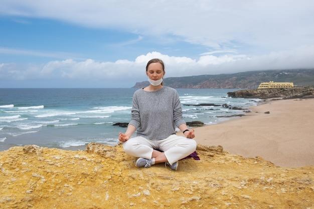 Tranquila mujer con mascarilla, meditando en postura de loto