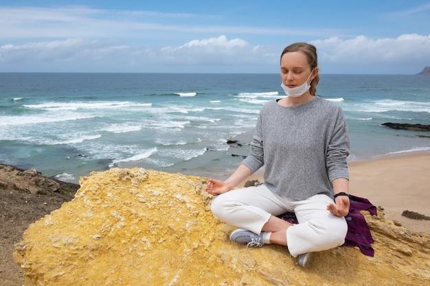 Tranquila mujer en mascarilla practicando yoga