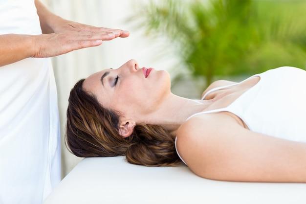 Tranquila mujer recibiendo tratamiento de reiki