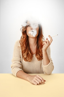 Tranquila mujer sentada y fumando descansando en la mesa.