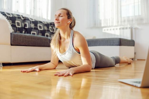 Tranquila, mujer yogui en pose de cobra yoga después de una conferencia en línea en casa.