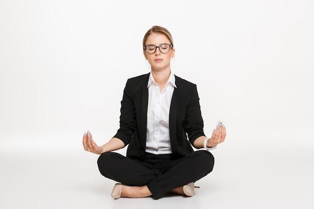 Tranquila rubia mujer de negocios en anteojos meditación en estudio con los ojos cerrados sobre la pared blanca