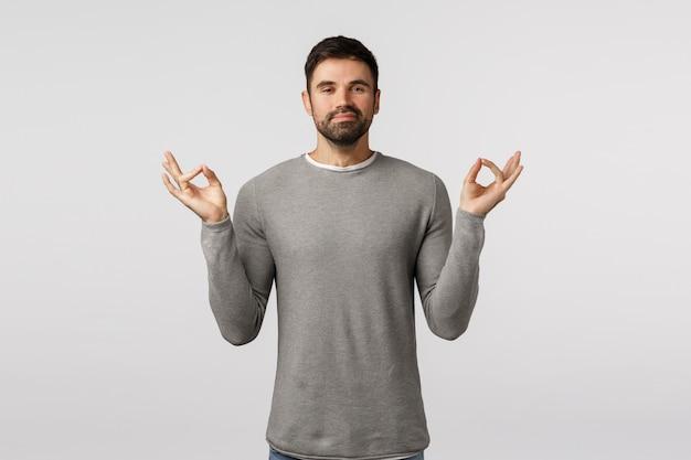 Tranquilo y alegre, sonriendo feliz hombre barbudo con suéter gris, sintiéndose bien después de la meditación, aliviar el estrés, tomarse de las manos de lado, mudra, gesto zen, alcanzar el nirvana, practicar yoga