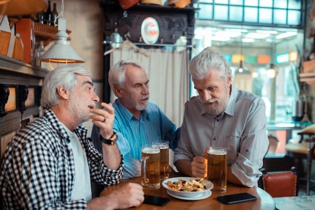 Tranquilo amigo. hombre jubilado de pelo gris calmando a su amigo después de perder su tiempo