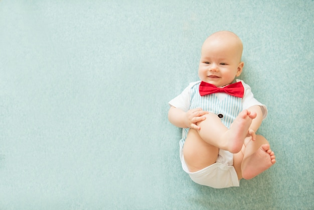 Tranquilo bebé curioso acostado sobre fondo azul, vista superior