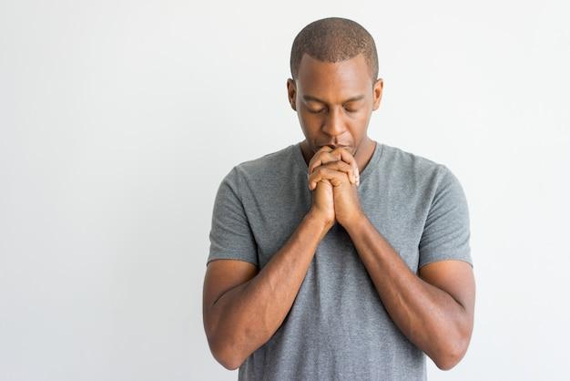 Tranquilo chico africano guapo espiritual rezando con los ojos cerrados.