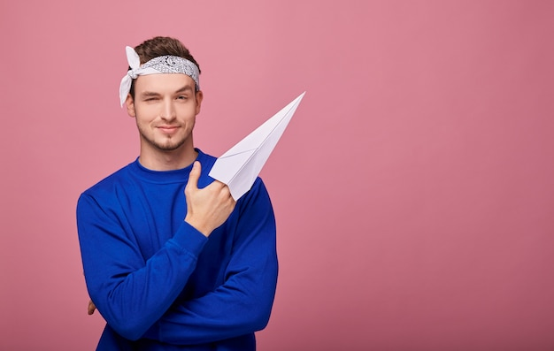 Tranquilo chico feliz en suéter azul oscuro de bandanin tiene avión de papel blanco en la mano y muestra a la izquierda