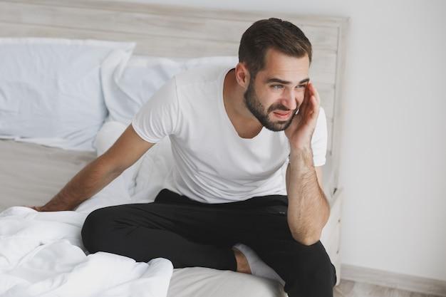 Tranquilo joven apuesto barbudo sentado en la cama con sábana blanca manta de almohada en el dormitorio en casa