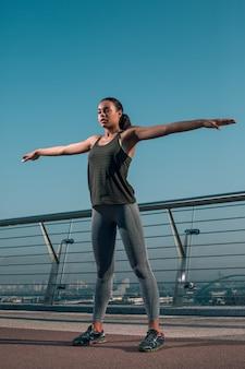 Tranquilo joven atleta de pie en el puente con las manos hacia los lados mientras hace ejercicio