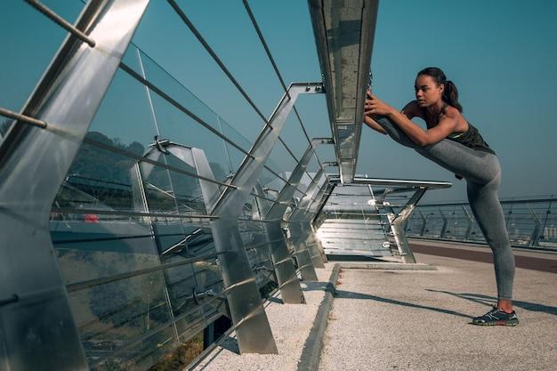 Tranquilo joven atleta poniendo un pie en la barandilla del puente y estirando los músculos de la pierna