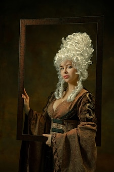 Tranquilo. retrato de mujer joven medieval en ropa vintage con marco de madera sobre fondo oscuro. modelo femenino como duquesa, persona real. concepto de comparación de épocas, moderno, moda, belleza.