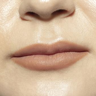 Tranquilo. sesión de primer plano de la boca femenina con maquillaje de labios de brillo nude natural y piel de las mejillas bien cuidada.