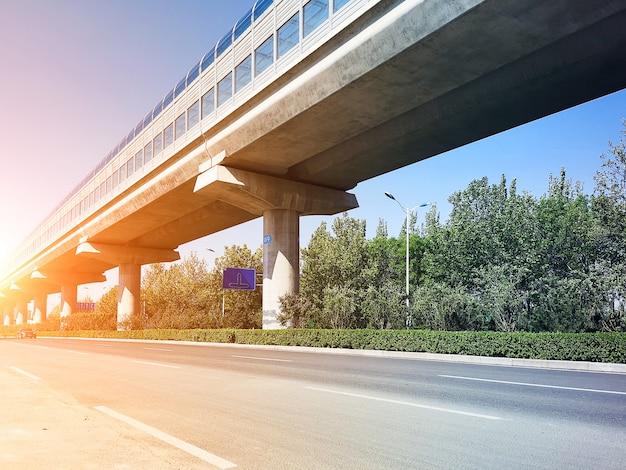 Tránsito de ferrocarril ligero de alta velocidad con muro de aislamiento acústico bajo cielo azul