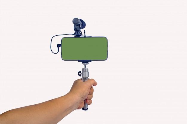 Transmisión de video en vivo con teléfono inteligente y herramienta de micrófono en la mano.