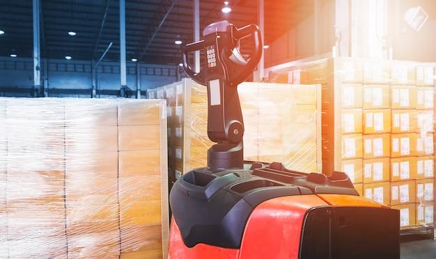 Transpaleta eléctrica de carretilla elevadora con cajas de paquetes en el almacén de almacenamiento almacén de envío de carga