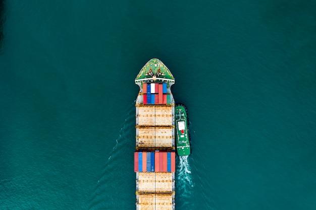 Transporte de contenedores de carga de envío en la vista aérea del mar verde