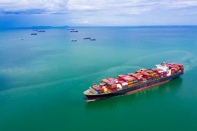 Transporte de contenedores de carga en la vista aérea del mar verde