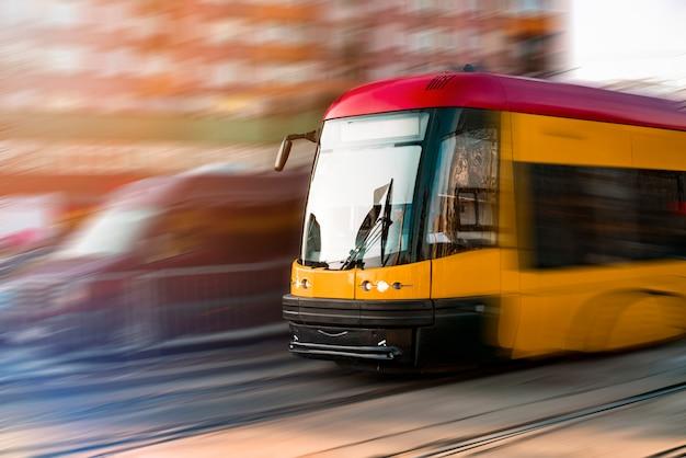 Tranvía amarillo con efecto de desenfoque de movimiento se mueve rápido en la ciudad