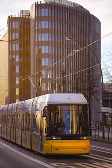 Tranvía de transporte público amarillo pasando por la ciudad de berlín, alemania