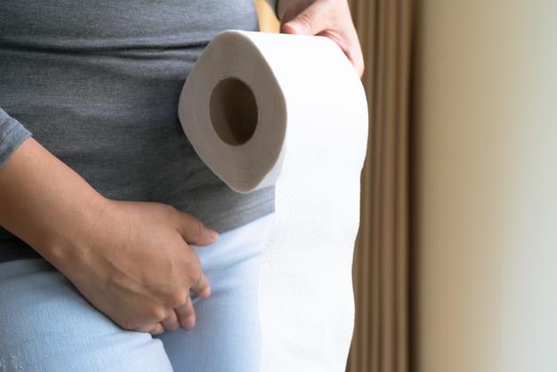 Trastorno, diarrea, incontinencia. concepto de salud. mano de mujer sosteniendo su entrepierna inferior abdomen y tejido o rollo de papel higiénico.
