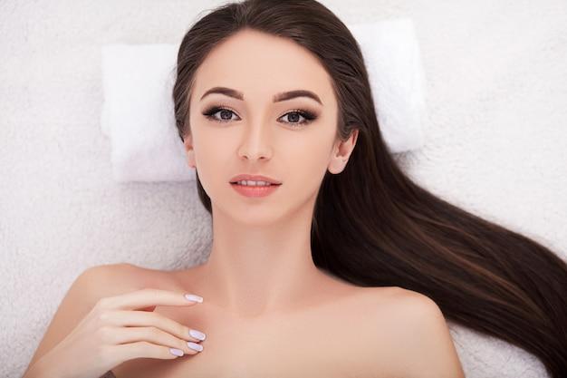Tratamiento de belleza facial. primer plano de una hermosa mujer que recibe tratamiento de belleza, masaje de manos en el day spa salon. massauer masajeando rostro femenino con aceite de aromaterapia. cuidado de la piel y el cuerpo. alta resolución