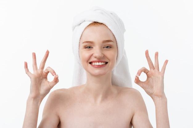 Tratamiento de belleza. mujer aplicando crema hidratante producto para el cuidado de la piel en la cara, haciendo un signo bien