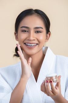 Tratamiento de belleza con mujer sostiene una crema hidratante en la mano