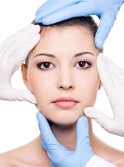 Tratamiento de belleza del rostro femenino hermoso joven aislado en blanco