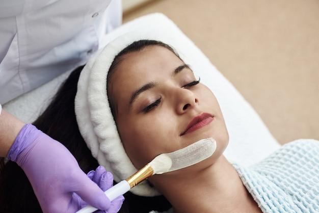 Tratamiento de belleza spa, cuidado de la piel. joven cosmetóloga aplicando mascarilla facial con pincel en spa