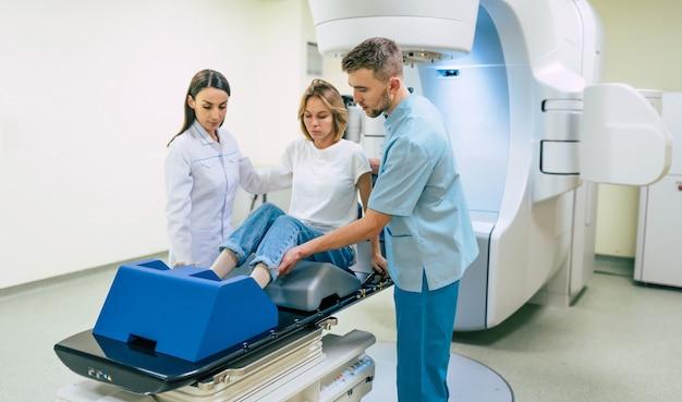 Tratamiento del cáncer en una clínica u hospital privado médico moderno con un acelerador lineal. equipo de médicos profesionales que trabajan mientras la mujer se somete a radioterapia para el cáncer