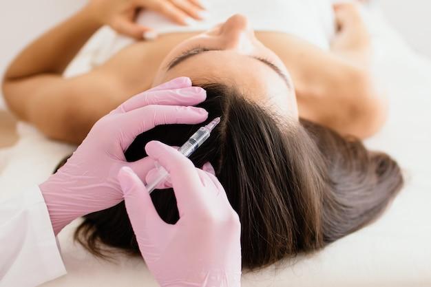Tratamiento capilar en cosmetología mediante inyección de mesoterapia en la cabeza.