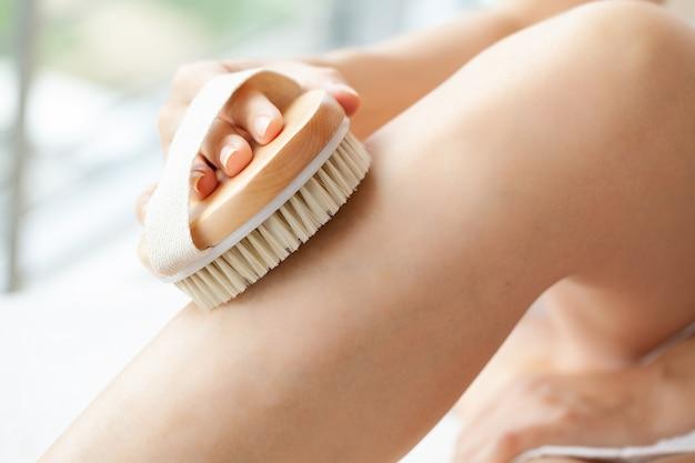 Tratamiento de celulitis, brazo de mujer sosteniendo un cepillo seco a la pierna.