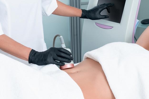 Tratamiento de contorno corporal con cavitación por ultrasonido. mujer recibiendo terapia anticelulítica y anti-grasa en la pierna en un salón de belleza
